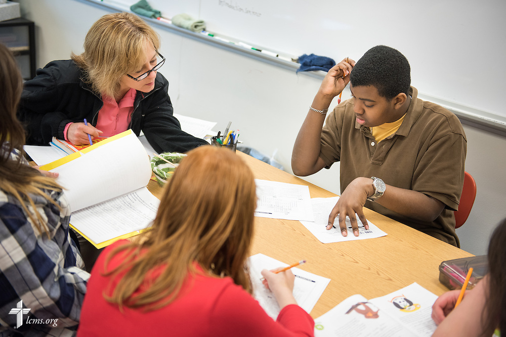 Student Samuel Gulliford solves a problem as Teacher Jill Bell reviews student work during class at Lutheran Special School & Education Services, located in Milwaukee Lutheran High School, on Tuesday, May 19, 2015, in Milwaukee, Wis. LCMS Communications/Erik M. Lunsford