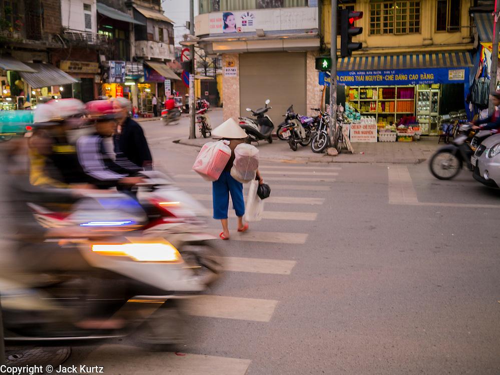 30 MARCH 2012 - HANOI, VIETNAM:   An elderly woman crosses a street in the Old Quarter of Hanoi, Vietnam.  PHOTO BY JACK KURTZ