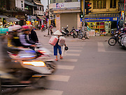 30 MARCH 2012 - HANOI, VIETNAM:   An elderly woman crosses a street in the Old Quarter of Hanoi, Vietnam.  PHOTO BY JACK KURTZ