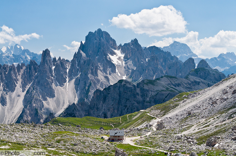 "The peaks of the Cadini Group jut high above Rifugio Lavaredo in the Dolomites, near Cortina d'Ampezzo, Italy, Europe. In the Cadini di Misurina, Cima Grande rises to 2999 meters (9839 feet), between Cima Piccola 2857 m (9373 ft) and Cima Ovest or ""Western Peak"" 2973 m (9754 ft). Hike for spectacular views around Tre Cime di Lavaredo (Italian for ""Three Peaks of Lavaredo,"" or in German called Drei Zinnen, ""Three Merlons""). The Dolomites are part of the Southern Limestone Alps, in northern Italy, Europe. UNESCO honored the Dolomites as a natural World Heritage Site in 2009."