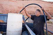 22 OCTOBER 2007 -- MONUMENT VALLEY, UT: AJ RYAN STANLEY, a Navajo Indian living on the Navajo reservation in northern Arizona, fills a 50 gallon water barrel with potable water at the well at Goulding's Trading Post in Monument Valley, UT. Stanley and his grandfather make daily trips to the well for potable water because they don't have a domestic water supply at their homestead. The well at Goulding's was first dug by Seventh Day Adventists missionaries  and is the only source of clean, free water for miles around. More than 30 percent of the homes on the Navajo Nation, about the size of West Virginia and the largest Indian reservation in the US, don't have indoor plumbing or a regular supply of domestic water. Many of these homes have to either buy water from commercial vendors or haul water from public wells. A Federal study showed that the total cost of hauling water was about $113 per 1,000 gallons. A Phoenix household, in comparison, pays just $5 a month for up to 7,400 gallons of water. The lack of water on the reservation means the Navajo are among the most miserly users of water in the United States. Families that have to buy or haul water use only about 15 gallons of water per day per person. In Phoenix, by comparison, the average water use is about 170 gallons per day.  Photo by Jack Kurtz