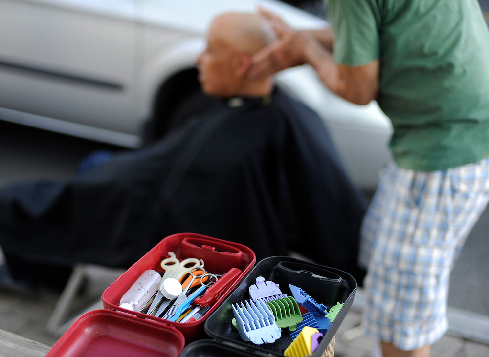 A set of clippers are scissors are within reach as Anthony Cymerys, known as Joe the barber works on a client in Hartford, Conn., Wednesday, May 1, 2013...