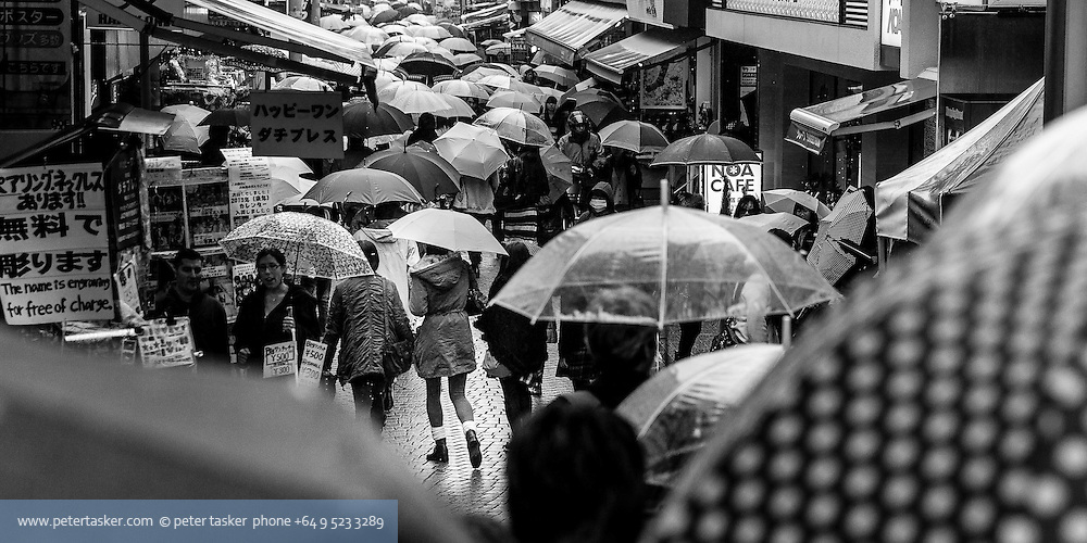Crowded street scene full of people with umbrellas, Japan.