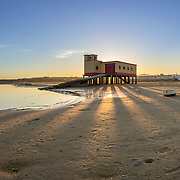 Sunset and historic life-guard building in the foreground, at Fuseta fishing town, Ria Formosa conservation park, Algarve. Portugal