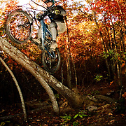 ASHEVILLE, NC - OCTOBER 28: A mountain biker launches of a tree on a trail in the Appalachian Mountains outside Asheville in North Carolina. (Photo by Logan Mock-Bunting) Mountain Biking