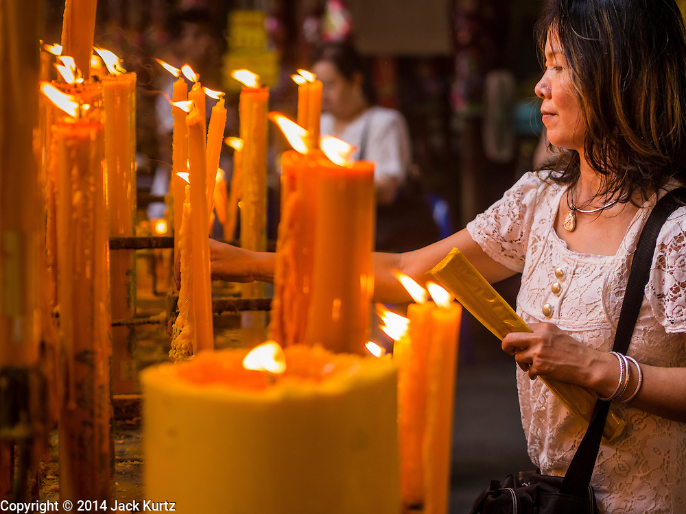 27 SEPTEMBER 2014 - BANGKOK, THAILAND:  A woman lights prayer candles during the celebration of the Vegetarian Festival at the Chow Su Kong Shrine in Talat Noi, a Chinese enclave in Bangkok. The Vegetarian Festival is celebrated throughout Thailand. It is the Thai version of the The Nine Emperor Gods Festival, a nine-day Taoist celebration beginning on the eve of 9th lunar month of the Chinese calendar. During a period of nine days, those who are participating in the festival dress all in white and abstain from eating meat, poultry, seafood, and dairy products. Vendors and proprietors of restaurants indicate that vegetarian food is for sale by putting a yellow flag out with Thai characters for meatless written on it in red.   PHOTO BY JACK KURTZ