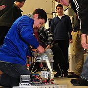BRUNSWICK, Maine --  12/17/13 -- Kyle Bonti of Kennebunk High School adjusts his team's  with a competition robot at  Southern Maine Community College (SMCC) last Tuesday. High School Students from Portland, Lewiston and Kennebunk gathered at SMCC's Brunswick center for their first robotics competition. A Bank of America grant to Portland and Lewiston started them up last spring -- giving an opportunity for young adults to work in teams to conceive, build, program and operate the small robots.  Photo © Roger S. Duncan 2013.