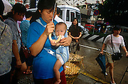 A Macanese mother carries her baby in a sling on her chest while shopping for supplies in a Macau market, China.