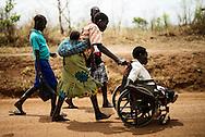 Invalid. Filda Ajok, 32, fik polio, mens hun boede i flygtningelejren Acholibur Camp. Hun bor stadig, hvor lejren lå, før den officielt blev lukket i 2007. Hendes børn hjælper hende med at komme ind til byen i kørestolen, som er svær at køre alene på de sandede veje. Hendes mand Afngo Ajok arbejder som daglejer