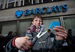 © licensed to London News Pictures. London, UK 10/02/2012. A protester cuts up her Barclays Bank debit card outside a branch of Barclays Banks in central London on February 10th, 2012, during a protest in support of the 'Move Your Money UK' campaign. Barclays today (10/02/2012) announces its annual results. Photo credit: Tolga Akmen/LNP
