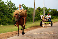 Horse and cart and man on a horse with a sack of hay in Chorro de Maita, Holguin, Cuba.