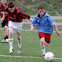 Holy Family's Tommy McCarty gets away from Ennis N.S Steven Murphy at the Ribena  5 aside national soccer blitz in Lees Road on Wednesday.<br /><br /><br /><br />Photograph by Yvonne Vaughan.