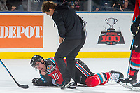 KELOWNA, CANADA - OCTOBER 27: Kelowna Rockets' Athletic Therapist Scott Hoyer comes on the ice to attend to Erik Gardiner #12 of the Kelowna Rockets after being hit in the side of the helmet by a puck against the Tri-City Americans on October 27, 2017 at Prospera Place in Kelowna, British Columbia, Canada.  (Photo by Marissa Baecker/Shoot the Breeze)  *** Local Caption ***