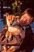 A Japanese woman shows off her Akita-Ken dog in the grounds of Hokkaido Jingu, Sapporo, Hokkaido, Japan.