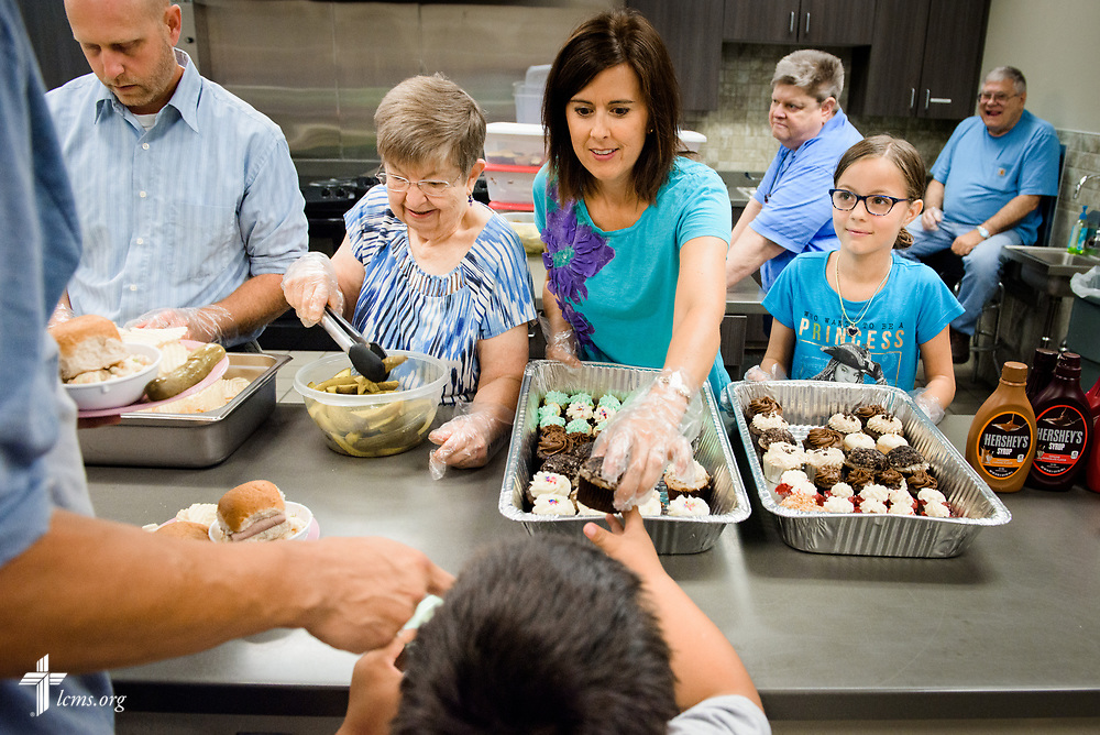 """Volunteers including Angie Schlenker (center) and her daughter Samantha volunteer join the Rev. Cory Aker, pastor of Faith Lutheran Church, Sioux Falls, SD., as they serve lunch at the Bishop Dudley Hospitality House homeless shelter on Tuesday, Aug. 1, 2017, in Sioux Falls. The meals are provided by a grant through the """"Stand With Your Community"""" program, which was made possible by a partnership between the LCMS, Thrivent Financial and Lutheran Church Extension Fund. LCMS Communications/Erik M. Lunsford"""