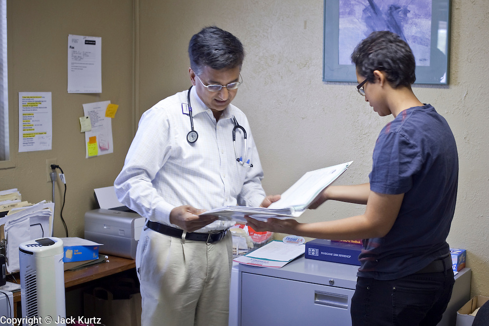 20 JUNE 2009 - PHOENIX, AZ: Dr. Naved Khan, left, a volunteer doctor at the Cultural Cup, talks to Sarrah Maher, the volunteer office manager at the clinic. The walk in clinic at the Cultural Cup Food Bank started two years ago when Cultural Cup founder Zarinah Awad wanted to expand the food bank's outreach and provide basic medical care for the people who use the food bank. The clinic sees, on average, 7 - 11 patients a week. Awad said that as the economy has worsened since the clinic opened and demand has steadily increased. She attributes the growth to people losing their jobs and health insurance. The clinic is staffed by volunteers both in the office and medical staff. Adults are seen every Saturday. Children are seen one Saturday a month, when a pediatrician comes in. Awad, a Moslem, said the food bank and clinic are rooted in the Moslem tradition of Zakat or Alms Giving, the giving of a small percentage of one's income to charity which is one of the Five Pillars of Islam.   PHOTO BY JACK KURTZ