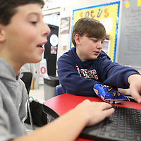 "Will Baker,12, points out a spot on the screen of fellow classmate Lewis Herman's, 12, computer as they write code while playing the ""Flappy Bird"" game during the Hour of Code Friday at Milam. The two had to write the proper code to get the bird through the game to gain points. The hour of code is a global event introducing tens of millions of students worldwide to computer science. The coding uses activities, characters, and challenges students are familiar with like a Star Wars and Mindcraft to initiate student interest in learning the language of coding."