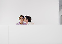 Man kissing female colleagues cheek in office cubicle
