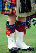 Scottish piper wearing tartan kilt, white gaiters, sporran and with dirk (knife) tucked in h is sock at the Braemar Games highland gathering  in Scotland.
