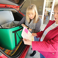 Lynn Johnson, coordinator of Traceway's Meals on Wheels looks over the days delivery list with Colita Corder, a Meals on Wheels volunteer, as they load up meals in Corder's car for her daily route.