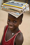Girl carrying schoolbooks on her head in the village of Essaout, Senegal, on Thursday June 14, 2007.