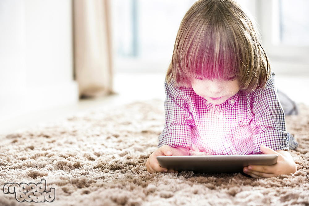 Boy using digital tablet while lying on rug at home