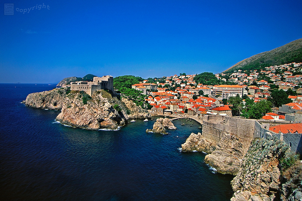 Looking down from a hilltop is a view of the harbor in Dubrovnik, Croatia and its fortress walls and red tiled rooftops. Located on the southern Dalmatian coastline, Dubrovnik, a UNESCO World Heritage Site is one of the most beautiful cities in the Mediterranean region.
