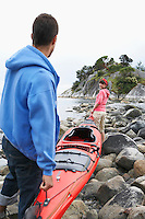 Couple carrying kayak to ocean