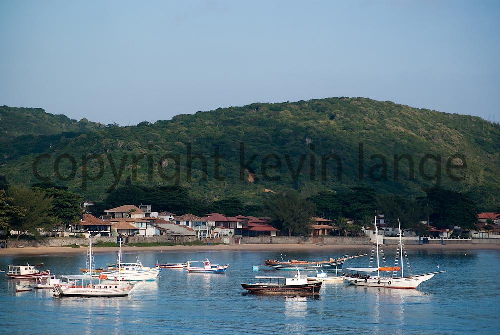 the ocean landscape marina of buzios, rio de janeiro, brazil with boats along the shore.  horizontal composition.