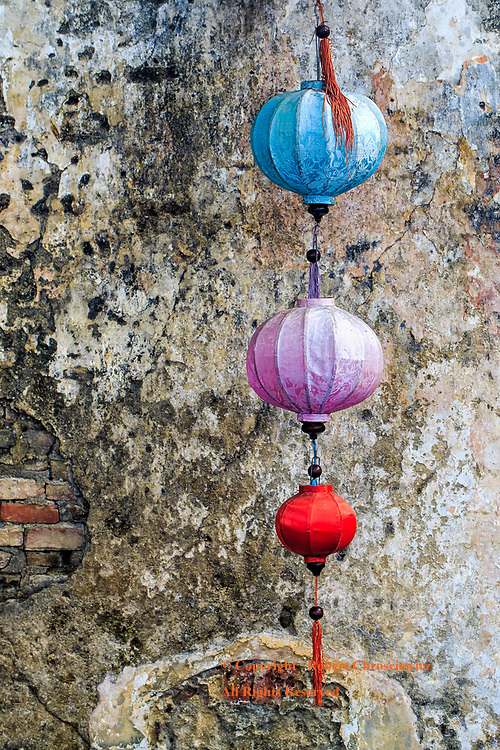 Lanterns: Hanging lanterns grace an old textured wall in Hoi An Vietnam.
