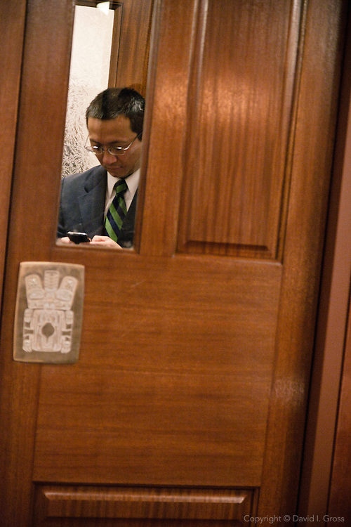 Rep. Scott Kawasaki (D)texts in the entrance to the Alaska State House of Representatives.