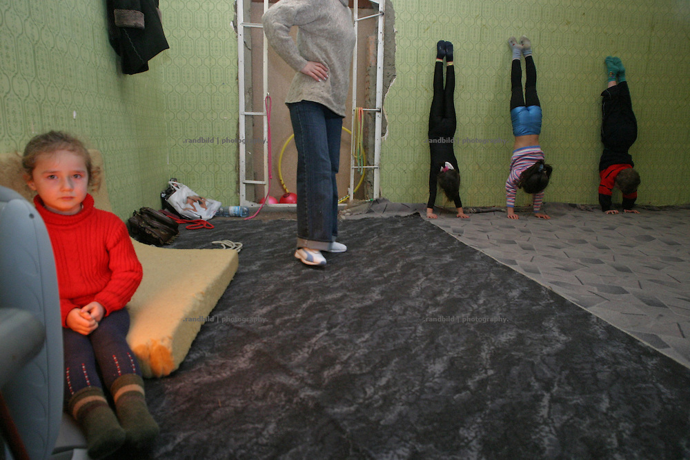"""In einer Gymnastik und Balletschule trainieren kleine Mädchen. Südossetien erklärte sich 1990 selbsständig und konnte den folgenden Sezessionskrieg gegen die Georgier für sich entscheiden. Zwischen Georgien und der abtrünnigen Region, die den Anschluß an die Russische Förderation fordert, kommt es trotz des Waffenstillstandsabkommens von 1992 immer wieder zu bewaffneten Ausseinandersetzungen. (Little girls trains at a Gymnastics and Ballet school. South Ossetia is a de facto independent republic located within the internationally recognized borders of Georgia. Although this former Soviet autonomous region has declared its independence in 1990. After the following civil war between georgians and ossetians ends in 1992, most parts of the territory is ossetian controlled, while some villages with georgian population are administrated by an georgian """"Alternative Government"""".)"""