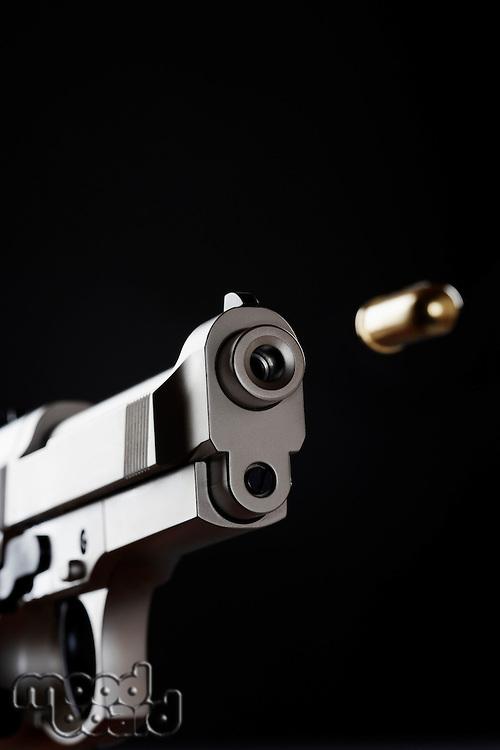 Gun shooting bullet on black background close up
