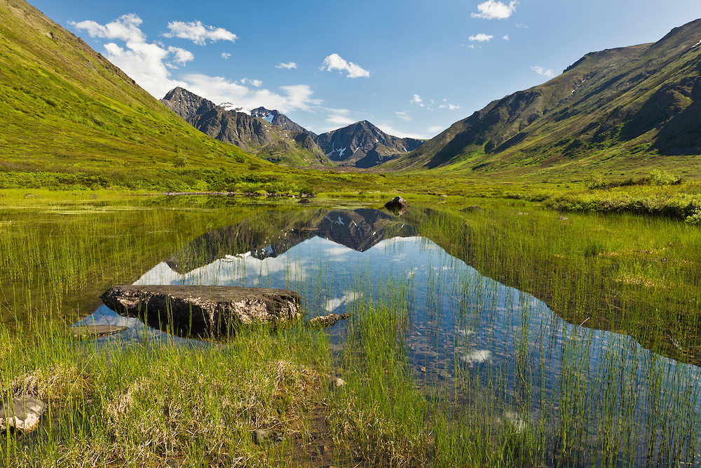Cantata Peak and Calliope Mountain are reflected in a pond along the South Fork Eagle River Valley in Chugach State Park in Southcentral Alaska. Summer. Afternoon.