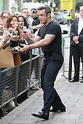 10.SEPTEMBER.2012. LONDON<br /> <br /> ROBBIE WILLIAMS AT THE STUDIOS OF BBC RADIO 1, WHERE A FAN GIVES HIM AND EVELOPE WITH A PLEA FOR A FREE TICKET TO ONE OF HIS GIGS.<br /> <br /> BYLINE: EDBIMAGEARCHIVE.CO.UK<br /> <br /> *THIS IMAGE IS STRICTLY FOR UK NEWSPAPERS AND MAGAZINES ONLY*<br /> *FOR WORLD WIDE SALES AND WEB USE PLEASE CONTACT EDBIMAGEARCHIVE - 0208 954 5968*