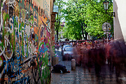 A begging man in-between the crowds of visitors close to the Prague Lennon Wall. Once a normal wall, since the 1980s it has been filled with John Lennon-inspired graffiti and pieces of lyrics from Beatles' songs.