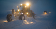 A Cruz Construction Inc. motor grader spreads ice chips near the end of the 27 mile long Prudhoe Bay - Badami ice road on Januray 24, 2013. The road to Badami is part of a longer winter-only corridor to the Point Thompson field.