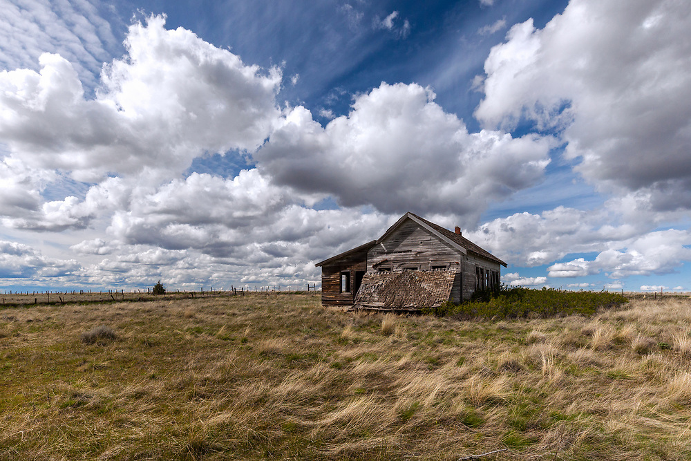An abandoned homestead sits under a big sky filled with dramatic cumulous clouds, on the high plains of north central Oregon.