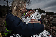 A volunteer helper comfort a crying baby as his family wait for transportation to a transit camp after they landed by rubber boats on the shores of Lesbos near Skala Sikaminias, Greece on 04 January, 2016. Lesbos, the Greek vacation island in the Aegean Sea between Turkey and Greece, faces massive refugee flows from the Middle East countries.