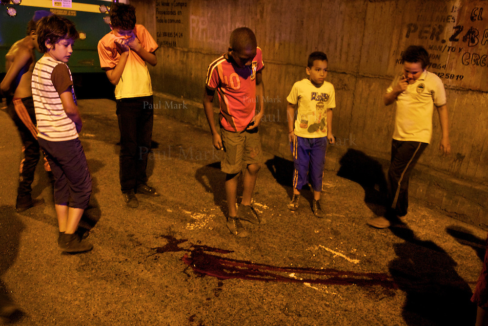 Children stand round a pool of blood after the body of a 16-year-old homicide victim was removed by police in the Andalucía neighborhood in Medellin's northeast.