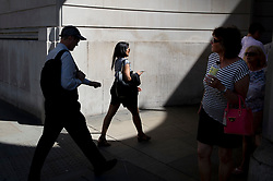 © Licensed to London News Pictures. 25/06/2018. London, UK. City workers and tourists pass through a circle of sunlight formed at the corner of the Bank of England as high temperatures remain in most of the UK. Photo credit: Peter Macdiarmid/LNP