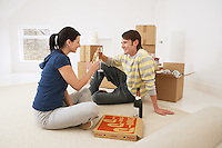 Couple in new home toasting with champagne and pizza