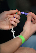 A rosary hangs from the hand of a teen attending the Wisconsin Catholic Youth Rally held March 24 at Mount Mary College in Milwaukee. (Photo by Sam Lucero)
