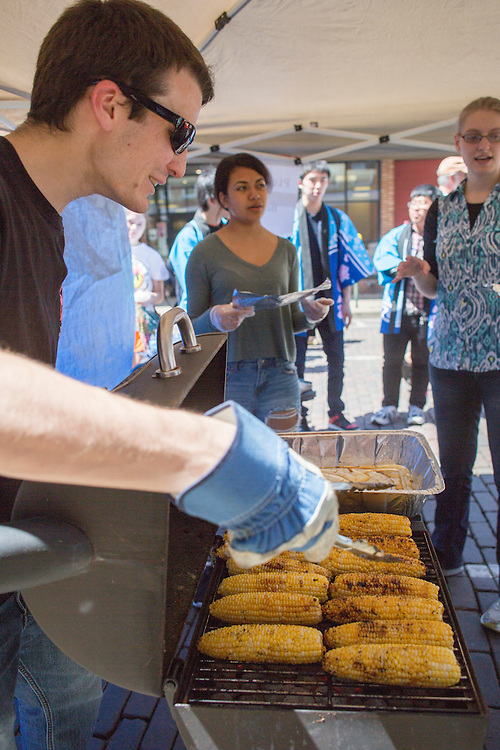 Evan Lewis, who will be the vice president of the Japanese Student Association next year, prepares grilled corn with soy sauce and sugar at the International Street Fair on April 14, 2016.