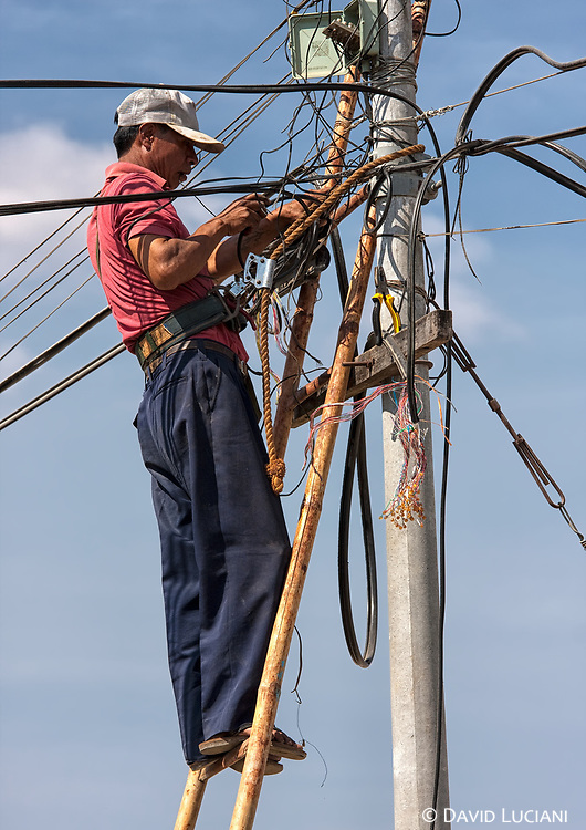 A man fixing a cable on a telephone pole along a street in Nyaung Shwe.