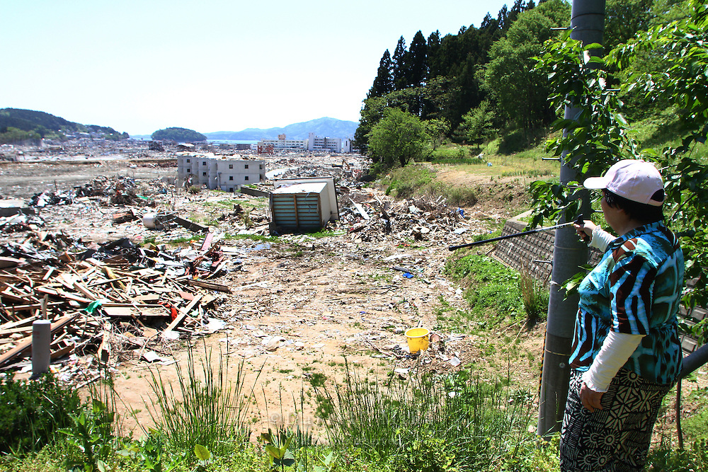 May 17, 2011; Minamisanriku, Miyagi Pref., Japan - Kuniko Suzuki stands near the area where she was firemen lucked her out of the tsunami flood waters on a hill just above Minamisanriku after the Great East Japan Earthquake and Tsunami in the Tohoku region of Japan.
