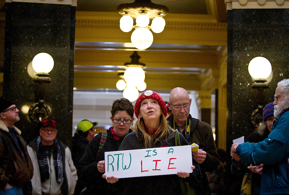 MADISON, WI — FEBRUARY 24: Solidarity singer Karen Kinsley chants and holds a protest sign in the Rotunda of the Wisconsin State Capitol. Workers and labor unions rallied in opposition to a right-to-work bill being discussed in the state legislature.
