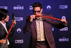 Cast member Robert Downey Jr. (R) tastes candied haws, a traditional Chinese sweet, at a promotional event of Hollywood superhero movie Iron Man 3 before its release in China in early May, in Beijing, capital of China, April 6, 2013. Photo by Imago / i-Images...UK ONLY.