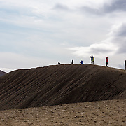 People standing on the rim of a tephra crater, looking down into the lake below. Silhouetted by a cloudy sky. Viti Crater, Myvatn, Iceland. July.