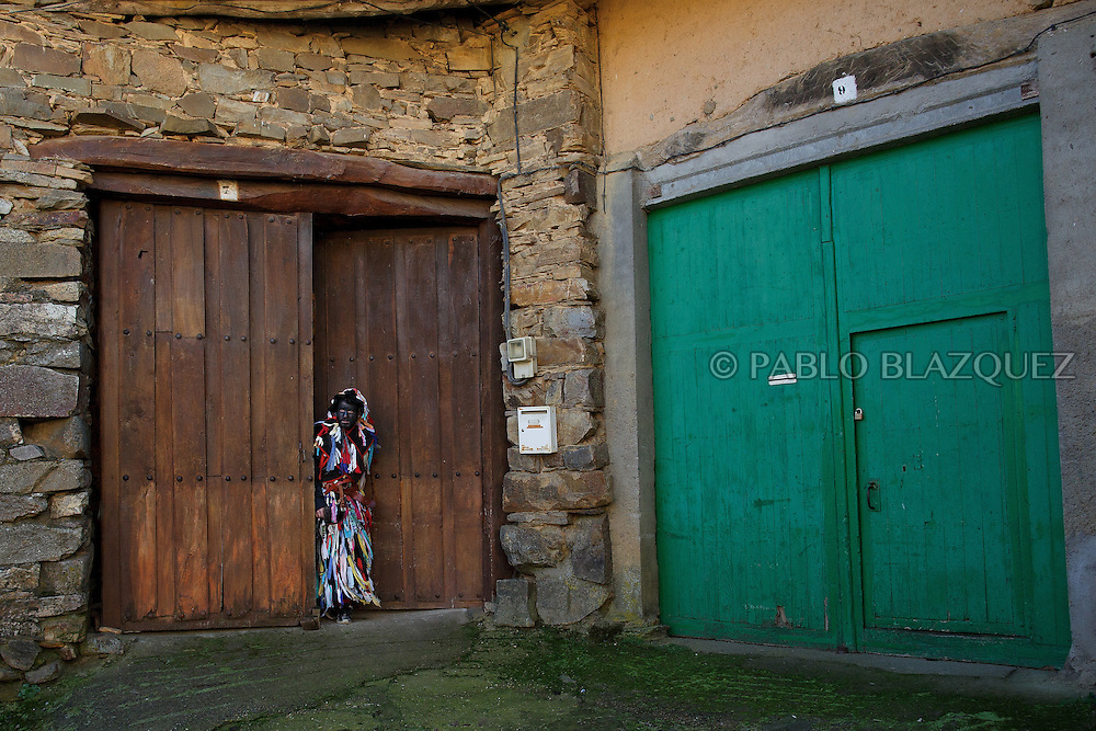 A man dressed as La Filandorra peeks out from the door of a house during La Filandorra festival on December 26, 2016 in the small village Ferreras de Arriba, Zamora province, Spain.  La Filandorra festival is a pagan winter masquerade that takes place during Saint Esteban festivities. The parade is represented by four characters, La Filandorra, El Diablo (Devil), La Madama (madame) y El Galán (Gallant). (© Pablo Blazquez)